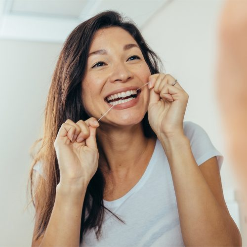woman flossing after scaling and polishing session